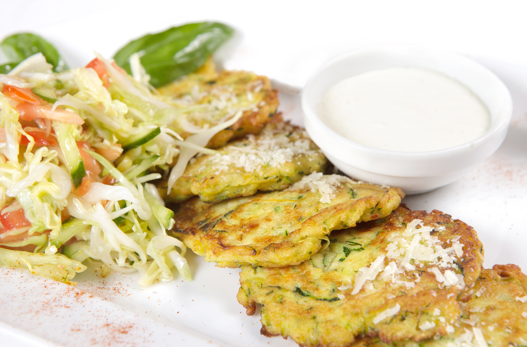 Close-up of zucchini fritters with parmesan cheese and lettuce o